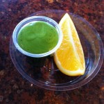 Wheatgrass Shot and a slice of Orange at Juicy Details Schiphol, Amsterdam